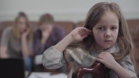Ledsen liten flicka för stående på stolen som ser i kameran och gråta Suddigt diagram av den unga kvinnan och den skäggiga mannen lager videofilmer