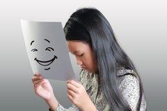 Ledsen liten flicka med den lyckliga framsidamaskeringen Arkivbild
