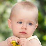 Ledsen liten flicka med en blomma i händerna Arkivbild