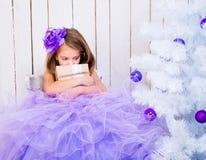 Ledsen liten flicka med en gåva Arkivfoto