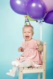 Ledsen liten flicka med locket och ballonger Arkivbild