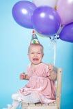 Ledsen liten flicka med locket och ballonger Fotografering för Bildbyråer