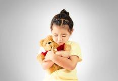 Ledsen liten flicka som kramar nallebjörnen bara royaltyfria foton