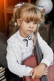 Ledsen liten flicka som rymmer en violoncell royaltyfria bilder
