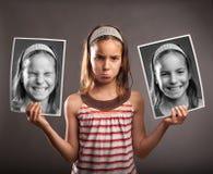 Ledsen liten flicka som rymmer två foto av henne Arkivfoton