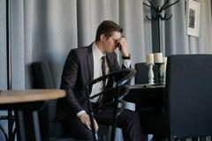 Ledsen man i ett sammanträde för affärsdräkt med en telefon i ett kafé honom rubbning för ` s arkivfoto