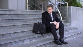 Ledsen man i trappa för kontorsbyggnad för affärsdräkt sittande, avskedandefördjupning lager videofilmer