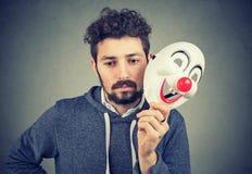 Ledsen man med clownmaskeringen royaltyfri foto