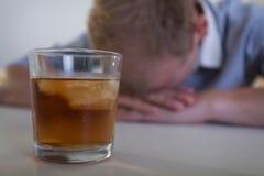 Ledsen man med ett exponeringsglas av whisky Royaltyfri Bild
