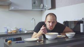 Ledsen man som äter pasta på tabellen Hem i hans kök Han oroar på grund av hans problem lager videofilmer