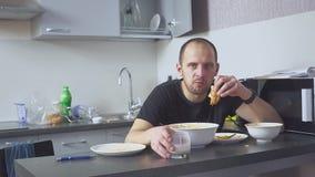 Ledsen man som äter pasta på tabellen Hem i hans kök Han oroar på grund av hans problem arkivfilmer