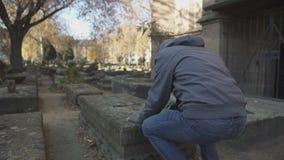 Ledsen man som ber nära grav på den forntida kyrkogården som firar minnet av familjen, utveckling stock video