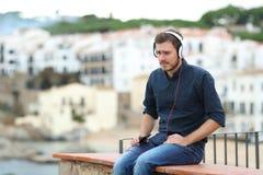 Ledsen man som lyssnar till musik på en avsats royaltyfri foto