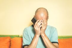 Ledsen man som rymmer hans mobiltelefon i hans händer, och skrik, därför att hans flickvän bryter upp med honom över textmeddelan royaltyfri bild