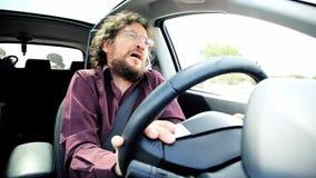 Ledsen man som sjunger i bil, medan desperat körning arkivfilmer