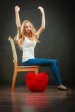 Ledsen melankolisk kvinna med den röda hjärtakudden arkivfoton