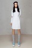 Ledsen modell i den vita klänningen i studio royaltyfri bild