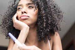 Ledsen och bekymrad kvinna med en graviditetstest på säng Arkivfoto