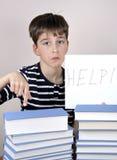 Ledsen och besviken ung pojke och böcker Arkivfoto
