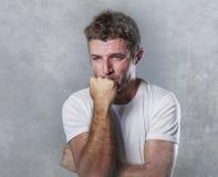 Ledsen och deprimerad man som biter hans desperata känsla för näve som frustreras och som är hjälplös i fördjupnings- och sorgsen royaltyfri foto