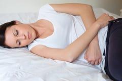 Ledsen och ensam kvinna som ligger i hennes säng arkivbilder