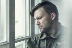 Ledsen och ensam soldat i fördjupning efter krig med emotionellt problem royaltyfri bild