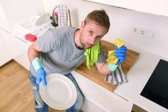 Ledsen och frustrerad man som tvättar disken och gör den hem- diskhon för att göra ren tröttad känsla royaltyfri bild
