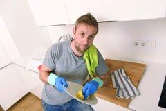 Ledsen och frustrerad man som tvättar disken och gör den hem- diskhon för att göra ren tröttad känsla royaltyfria bilder