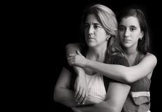 Ledsen och ilsken moder med dottern som omfamnar henne Royaltyfri Fotografi