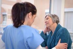 Ledsen patient med sjuksköterskan royaltyfria bilder