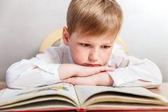 Ledsen pojke i ett vitt skjortasammanträde på hans skrivbord royaltyfri bild