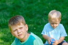 Ledsen pojke i trädgård Royaltyfri Foto