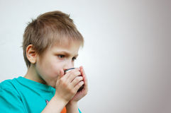 Ledsen pojke med den varma drinken, Royaltyfri Foto