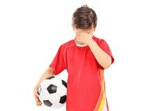 Ledsen pojke med fotbollbollen Arkivfoto