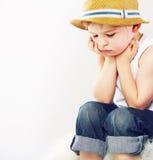 Ledsen pojke med hans sugrörhatt Arkivbild