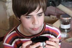 Ledsen pojke som dricker te Arkivfoto