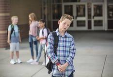 Ledsen pojke som känner sig lämnad ut, retad och trakasserad av hans klasskompisar arkivfoto