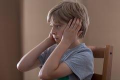 Ledsen pojke som pluggar öron Arkivbild