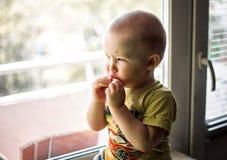 ledsen pojke som sitter nära fönster royaltyfri foto