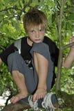 Ledsen pojke som spelar på ett träd Arkivbilder
