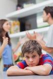 Ledsen pys som lyssnar till hans argumentera för föräldrar Arkivbild