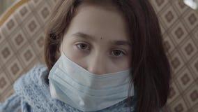 Ledsen sjuk flicka för Closeupstående med en steril maskering på hennes framsida som ner hemma ser Begrepp av ett sjukt barn Medi stock video