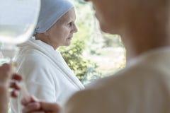 Ledsen sjuk hög kvinna med cancer under kemoterapi i sjukhuset royaltyfri foto