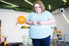 Ledsen sjukligt fet kvinna som mäter midjan fotografering för bildbyråer