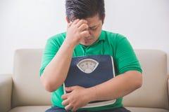 Ledsen sjukligt fet man som rymmer en viktskala som tänker om hans vikt arkivbild