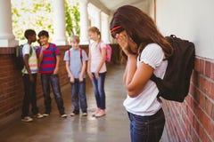 Ledsen skolflicka med vänner i bakgrund på skolakorridoren arkivbild