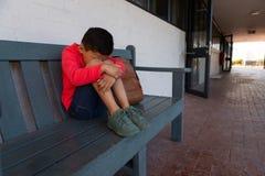 Ledsen skolpojke som bara sitter på bänk i korridor royaltyfria foton