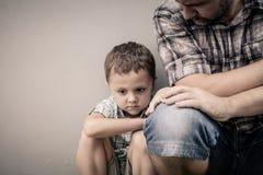 Ledsen son som kramar hans farsa Arkivfoto