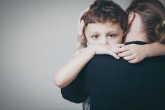 Ledsen son som kramar hans moder Royaltyfri Fotografi