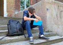 Ledsen student med boken fotografering för bildbyråer